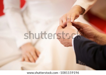 Wedding rings.He Put the Wedding Ring on Her.Close up Groom Put the Ring on bride. thai wedding ceremony and thai wedding decoration. #1081159196