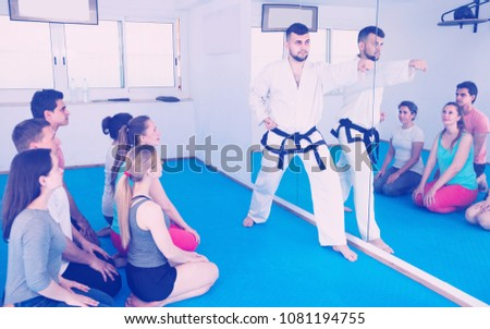 Smiling instructor is showing new martial moves to adults in karate class.  #1081194755