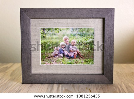A tabletop display of a rustic wood framed print holding a portrait of a family of three happy young children sitting outside on a summer day.