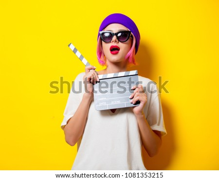 Young girl with pink hair in purple hat and sunglasses holding movie clapper on yellow background #1081353215