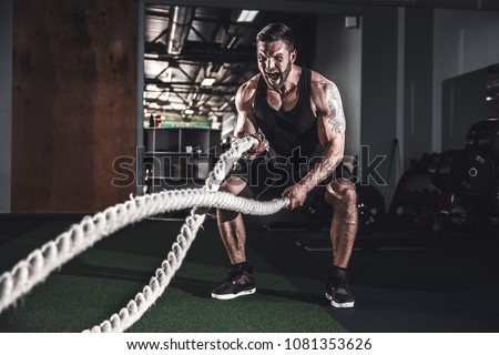 Muscular powerful aggressive man training with rope in functional training fitness gym #1081353626
