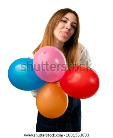 Beautiful young girl holding a balloon and taking out her tongue #1081353833