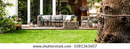 Wicker sofa with pillows and table with fruits and juice standing on garden terrace by the house with glass door #1081363607
