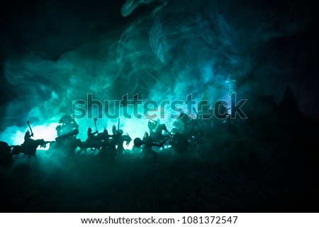 Medieval battle scene with cavalry and infantry. Silhouettes of figures as separate objects, fight between warriors on dark toned foggy background. Night scene. Selective focus Royalty-Free Stock Photo #1081372547