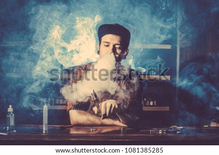 Punk hipster man is smoking a mechanical vape device. Toned image. The concept of popularization of vaping. Ecig rapairing process with cloud of steam horizontal #1081385285