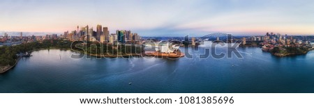 Sydney harbour around city CBD with famous landmarks and Sydney Harbour bridge at sunrise in aerial panorama. Royalty-Free Stock Photo #1081385696