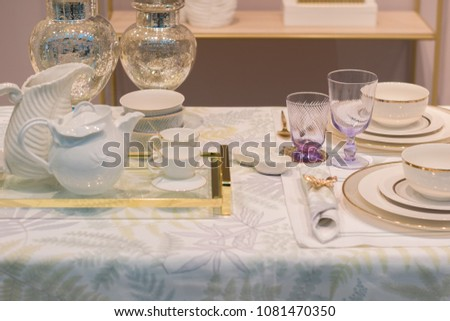 close-up luxury white and gold table set with glasses and tea se #1081470350