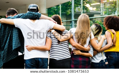 Smiling happy young adult friends arms around shoulder outdoors friendship and connection concept Royalty-Free Stock Photo #1081473653