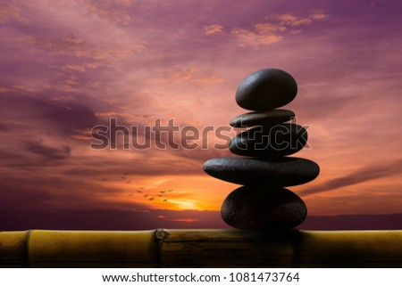 Balance Concept between of Life and work present by Natural Zen Rock Stack on Bamboo Wooden, Sunrise or Sunset Sky as background #1081473764