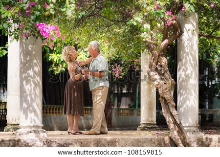 Active retired people having fun, happy old man and woman dancing latin american dance in patio #108159815
