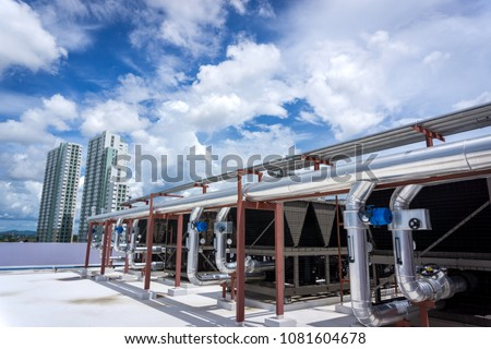The air conditioning chiller consists of a metal hose. All are mounted on the roof of the building. #1081604678