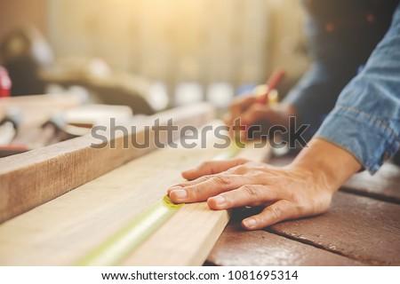 Carpenter working on woodworking machines in carpentry shop. woman works in a carpentry shop. #1081695314
