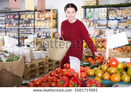 Young woman  choosing tomatoes  in farm food store #1081719881