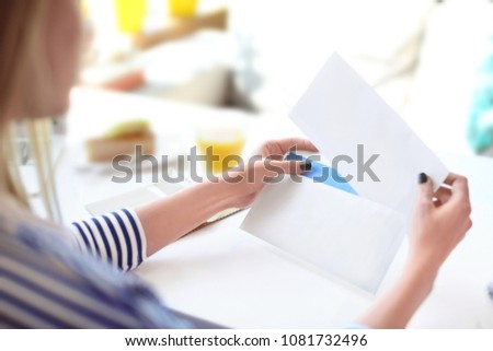 Young woman putting letter into envelope at table in cafe. Mail delivery Royalty-Free Stock Photo #1081732496