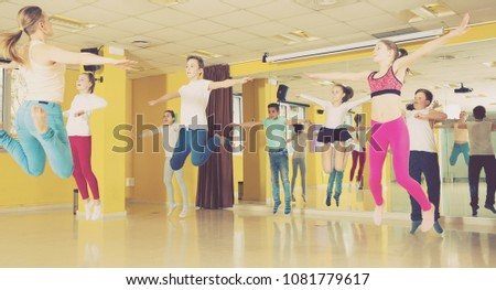 Group of tweens jumping with female coach during exercising in choreography class  #1081779617