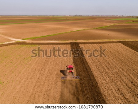 Aerial shot of a tractor cultivating field at spring #1081790870