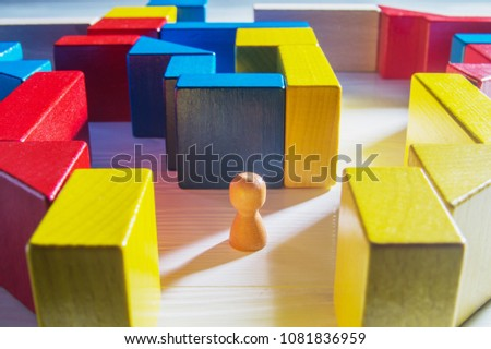 The man in the maze. The concept of a business strategy, analytics, search for solutions, the search output. Labyrinth of colorful wooden blocks. #1081836959