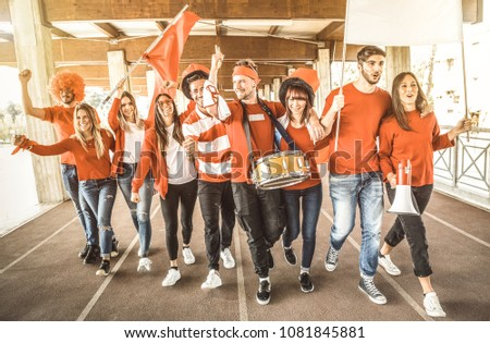 Football supporter fans friends cheering and walking to soccer cup match at intenational stadium - Young people group with red and white t-shirts having excited fun on sport world championship concept #1081845881