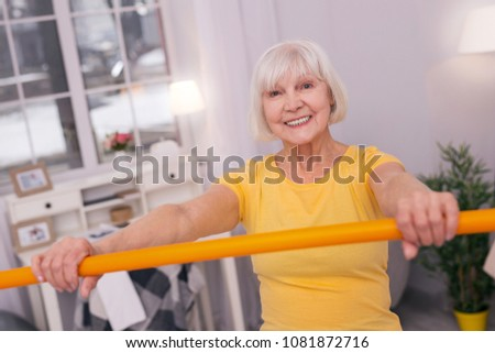 Great mood. Cheerful elderly woman in a yellow t-shirt holding a health bar in front of her and smiling happily at the camera #1081872716
