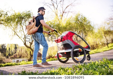 A father with jogging stroller on a walk outside in spring nature. #1081896095