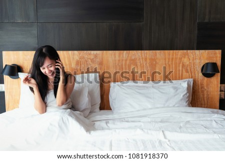 Young adult southeast Asian woman age 30s smiles and looks ecstasy while sitting on the bed holding and talking on the mobile phone. Copy space on the right. #1081918370