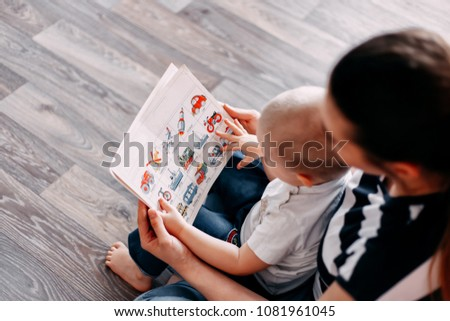 Mother is showing some pictures in a book to her son.