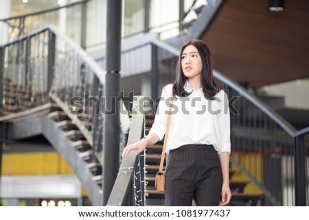 Young Asian business woman with casual uniform thinking while standing on the stair (business thinking or outside working concept) #1081977437