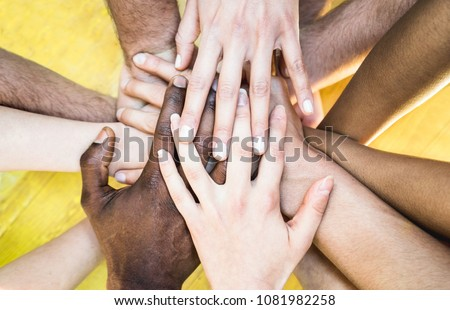 Top view of multicolored stacking hands - International friendship concept with multiethnic people representing peace and unity against racism - Multi racial love and integration between diversity #1081982258