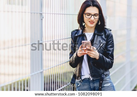 Girl messaging on phone and smiling outside #1082098091