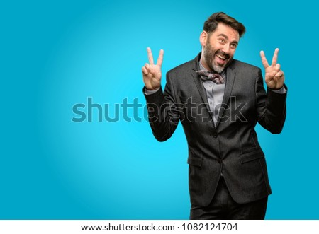 Middle age man, with beard and bow tie happy and excited expressing winning gesture. Successful and celebrating victory, triumphant #1082124704