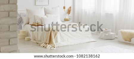 White bedroom interior with windows, gold accessories and white bedsheets on king-size bed #1082138162