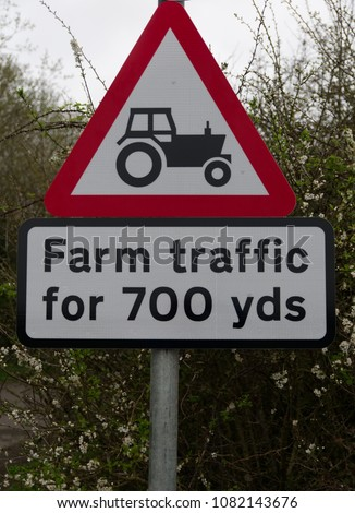 Red and white triangular road safety sign warning of farm traffic with picture of black tractor for 700 yards