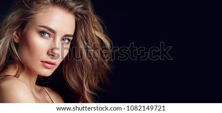 A beautiful tender girl in a silk top with beautiful long dark hair developing in the wind. Black background.fashion, beauty, makeup, cosmetics, beauty salon, style, personal care, posture, hair, styl #1082149721