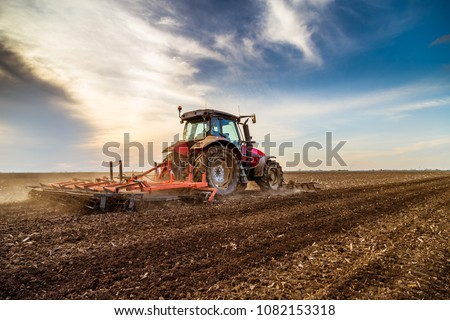 Tractor cultivating field at spring #1082153318
