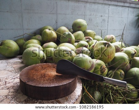 Big knife and wooden chopping block on marble table and green coconut background. #1082186195
