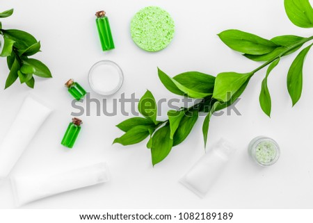 Organic skin care products. Cream, lotion, tonic. oil near green leaves on white background top view #1082189189