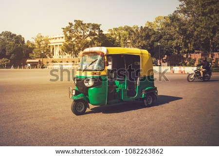 Moto-Rickshaw, New Delhi, India. Indian taxi stands on the street against backdrop of the presidential Palace. Expensive area of the city. Tricycle vintage retro motorcycle