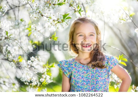 Happy little girl playing in spring cherry garden #1082264522