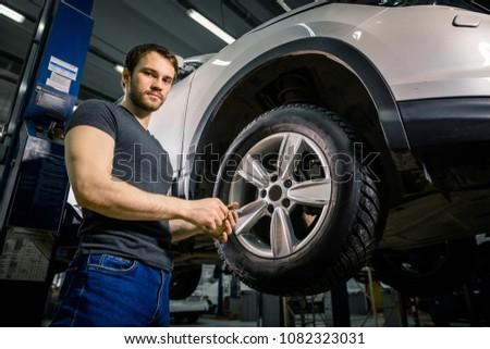 Mechanic preparing for adjusting tire wheel at repair garage #1082323031