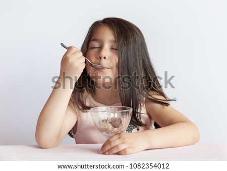 Happy child girl eating ice cream in white and chocolate bowl on white background. Enjoying delicious. Royalty-Free Stock Photo #1082354012