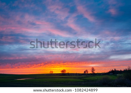 Bright sunset in the orange light over a rural field with a reflection of red on the clouds #1082424899