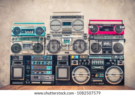 Retro old school design ghetto blaster stereo radio cassette tape recorders boombox tower from circa 1980s front concrete wall background. Vintage instagram style filtered photo #1082507579