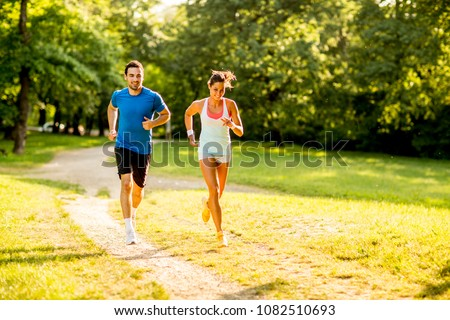 Young couple running outdoors in the park on a sunny day #1082510693