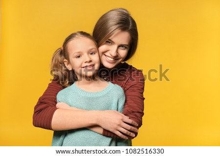 Portrait of mother and cute little daughter on color background #1082516330