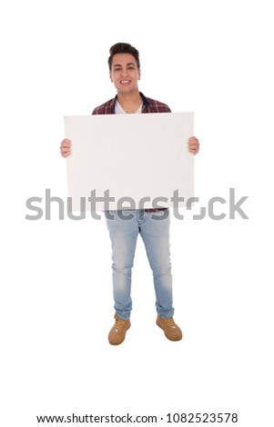 Full-length shot of young man standing and holding a white billboard in a Horizontal pose, isolated on a white background. #1082523578