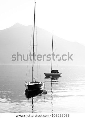 Two sail boats in early morning on the mountain lake. Black and white photography. Salzkammergut, Austria. #108253055