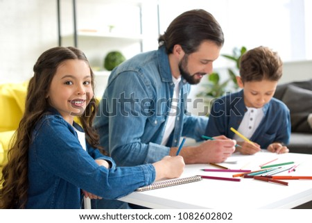adorable child smiling at camera while drawing with father and brother at home #1082602802