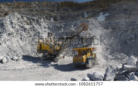 Heavy excavator loads ore in the body of a heavy dump truck, panorama. Mining industry. Heavy equipment. #1082611757