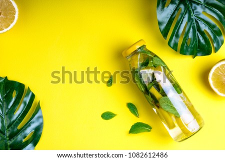 Monstera leaves and bottle tropical water on yellow background. Detox fruit infused water, citrus fruits and mint leaves. Top view, flat lay, copy space #1082612486
