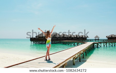 Young blond girl in a colored dress near water bungalows located in a small island of Maldives.Paradise background. Copy space. Banner for travel agency.  #1082634272